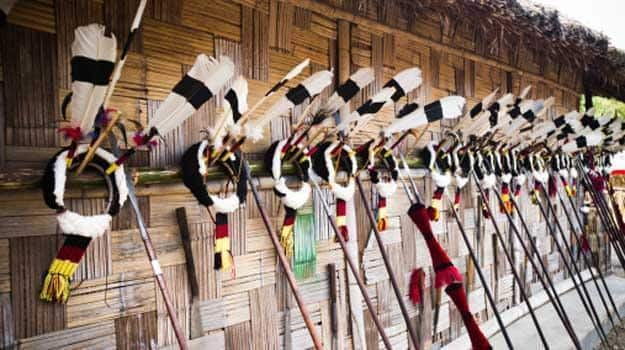 Feather headdresses with spears on the wall of a tribal hut in Kohima, Nagaland