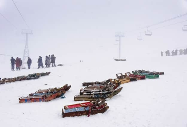 Colourful sleds parked on the pristine white snow, ready to carry tourists up the hill