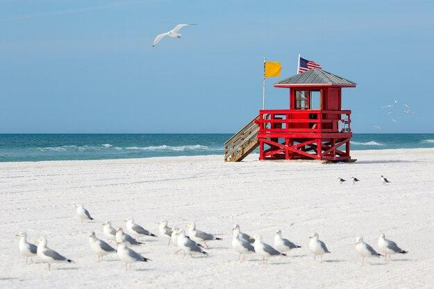 Red wooden lifeguard hut on an empty morning at Siesta Beach, Florida