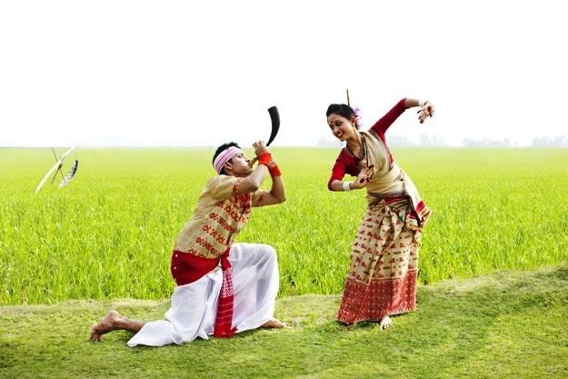 Bihu man blowing on a pepa while Bihu woman dances