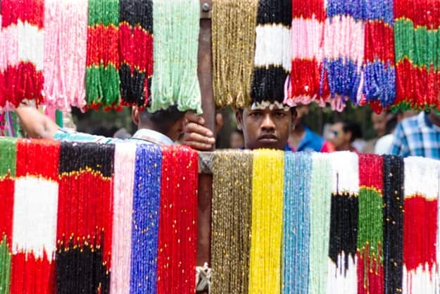 A street vendor looking through his colorful trinkets and necklaces at the street during Bengali New Year