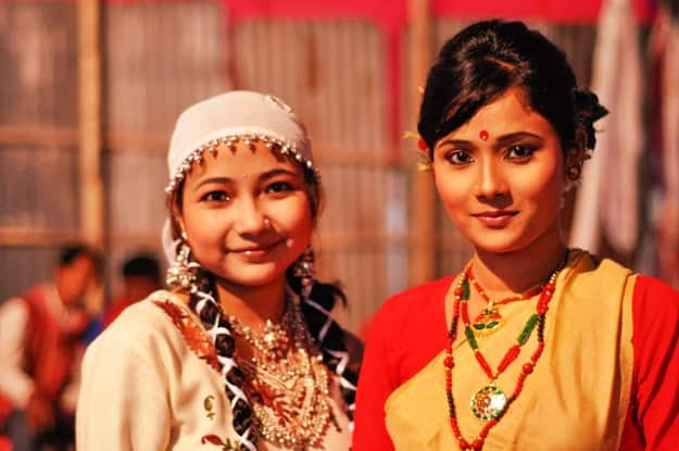 Two young women in traditional clothes smile at Bihu festival in Guwahati, Assam