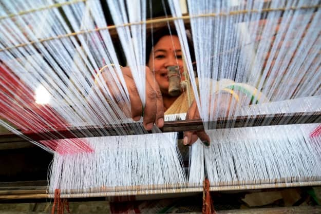 An Assamese woman busy in weaving traditional cloths on hand loom for Bihu festival