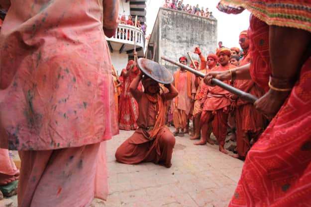 Women beat up men with long sticks as a ritual in the Lathmar Holi celebration