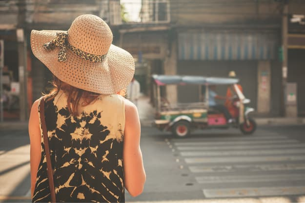 A young woman wearing a hat is walking in the streets of an asian countryA young woman wearing a hat is walking in the streets of an asian country