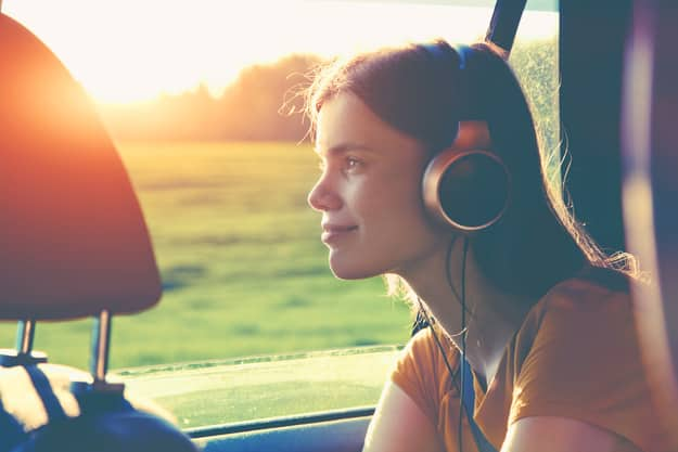 smiling pretty girl listening to music with headphones moving in car
