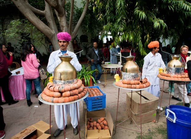 Men in traditional Rajasthan dresses prepare tea masala during the Jaipur Literature Festival