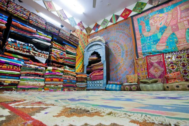 Interior of the textile store with colorful carpets, bedspreads and shawls in Jaipur
