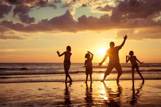 Father and children playing on the beach at the sunset time. Concept of friendly family