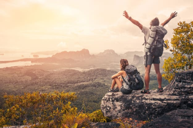 Hikers with backpacks relaxing on top of a mountain and enjoying the view of valley at sunset