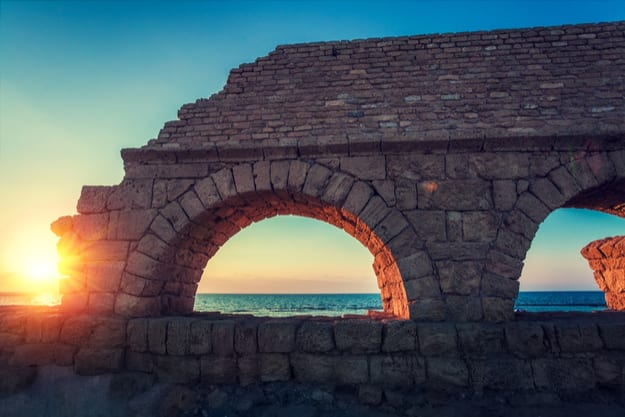 Remains of the ancient Roman aqueduct in ancient city Caesarea at sunset. Israel