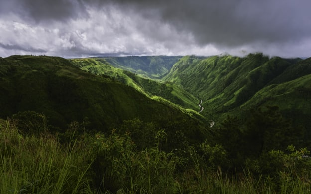 Storm clouds over the Khasi Hills as streaks of light break through the clouds to highlight the impressive contours of the mountains near Cherrapunjee, Meghalaya, India
