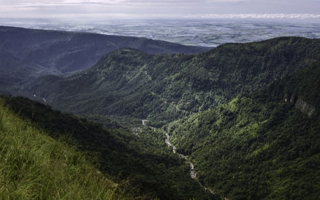A river flows along a deep gorge flanked by florested mountains of the Khasi range with Bangladesh visible on the horizon near Shillong, Meghalaya, India
