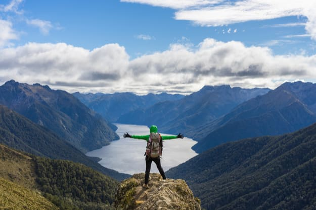 Woman hiker on mountain cliff, Kepler Track, New Zealand