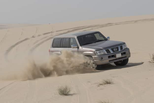 Driving a 4-wheel drive SUV on the desert in Inland Sea, Doha, Qatar