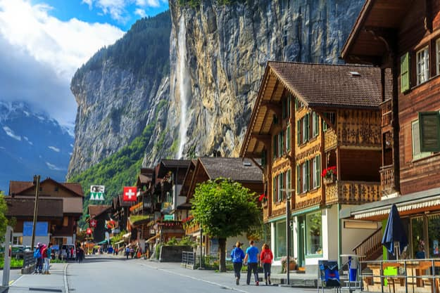 Spectacular principal street of Lauterbrunnen with shops,hotels,terraces,swiss flags and stunning Staubbach waterfall in background, Bernese Oberland, Switzerland