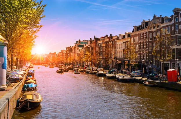 Traditional old buildings and and boats at the sunset in Amsterdam, Netherlands