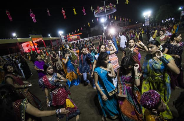 Female and male dancers in traditional colourful Indian costume dancing and playing Garba on the floor among crowd during Navratri in Ahmedabad, Gujarat