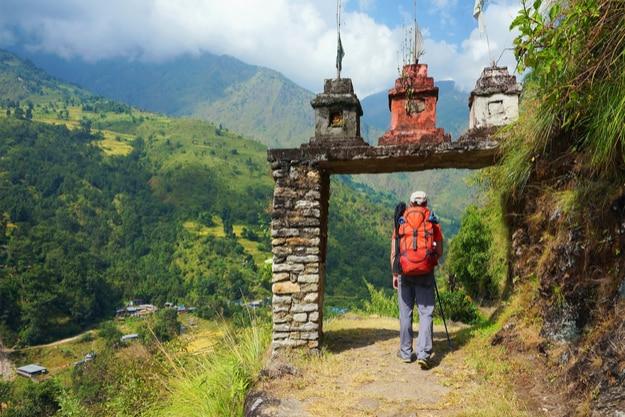 Tourist entering the gate to Nepalese village on Annapurna Circuit Trek