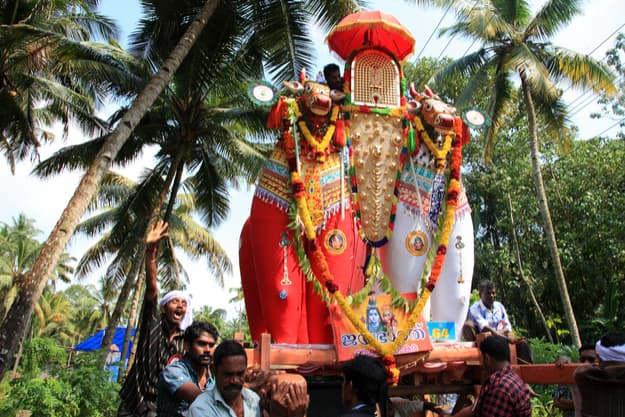 Devotees bring huge bullock effigies as a procession to Parabrahma temple during the temple festival in Oachira, Kerala