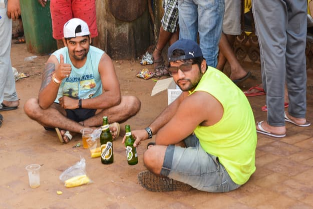 Men drink beer at the Calangute beach, November 2016