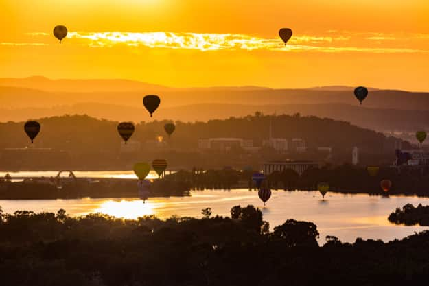 Hot air balloons are floating over the lake burley griffin in Canberra during sunrise