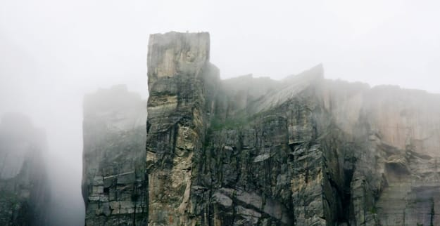 Preikestolen in Norway with persons seen from a distance on a dark day with a lot of fog