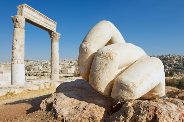 Stone Hercules hand at the antique Citadel in Amman, Jordan. At the background ruins of the Hercules temple and Amman city