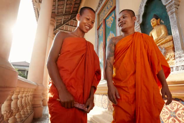 Two buddhist monks meeting and saluting in a temple, Phnom Penh