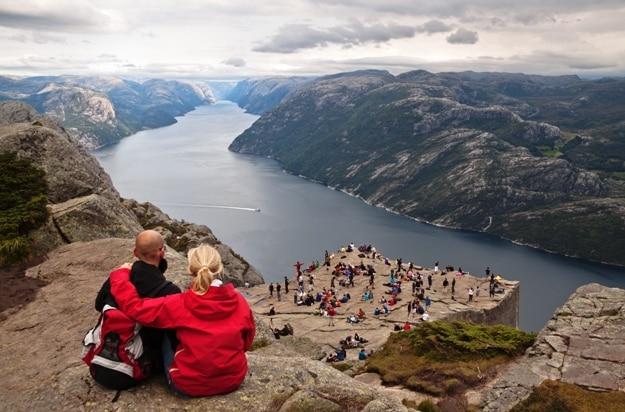 tourists enjoy breathtaking views from Preikestolen rock