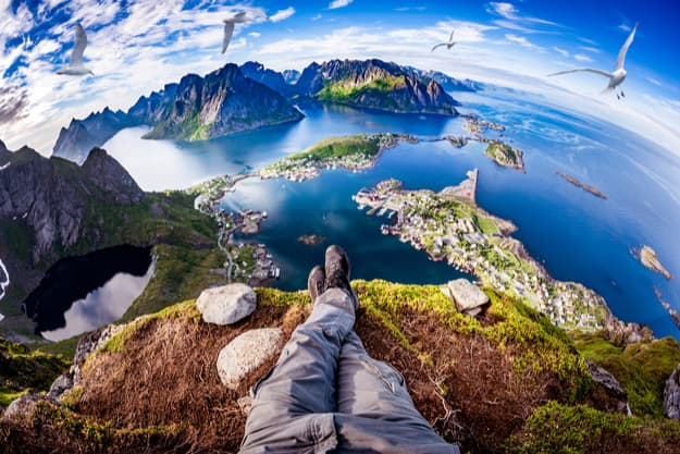 First person perspective shot from a hiker sitting at the edge of a cliff at Lofoten is an archipelago in the county of Nordland, Norway