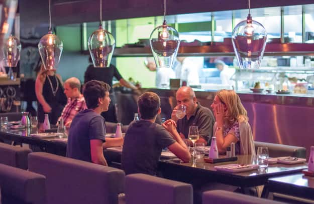 People having dinner in a modern and chik open kitchen restaurant in Israel. Part of the hip Sarona district featuring restored Templer buildings