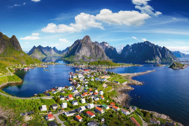 Reine, Lofoten, Norway. The village of Reine under a sunny, blue sky, with the typical rorbu houses