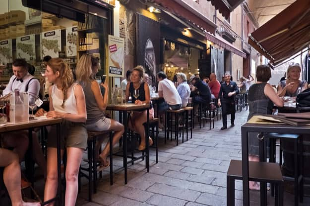 People enjoy an aperitif, eating and drinking traditional foods in Bologna, Italy