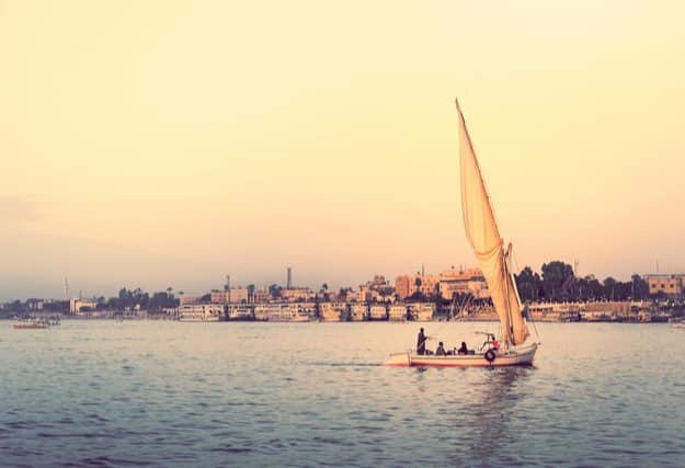 Felucca at sunset - travel on sail vessel on the Nile river, romantic cruise and adventure in Egypt. Traditional egyptian sailboat on horizon. Skyline of Luxor on riverside
