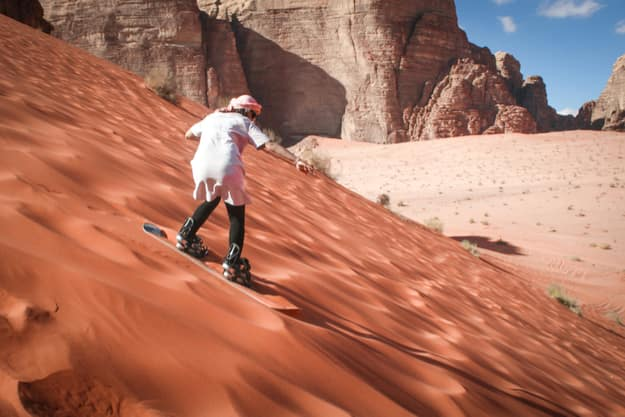 Girl sand boarding on dunes in Wadi Rum