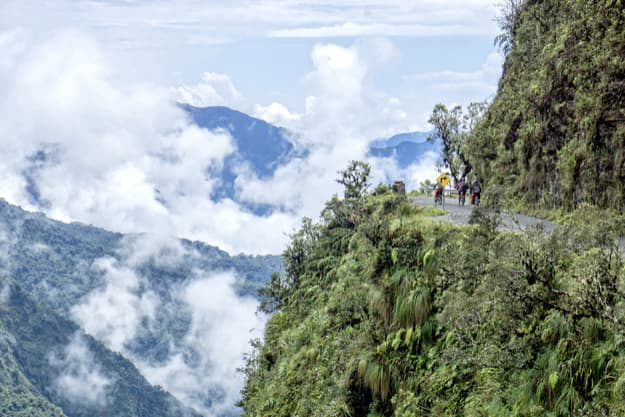 Mountain bikers riding the famous downhill trail Road of death in Bolivia