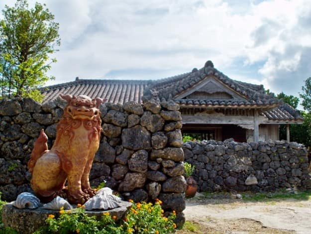 A traditional Okinawan house with large tiled roof,and shisa a traditional Ryukyuan decoration, often in pairs, resembling a cross between a lion and a dog.