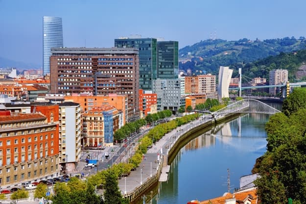 Aerial view of Bilbao, Spain city downtown with a Nevion River, Zubizuri Bridge and promenade. Mountain at the background, clear blue sky