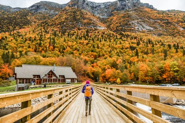 Autumn nature hiker girl walking in national park in Quebec with backpack. Woman tourist going camping in forest. Canada travel hiking tourism at Hautes-Gorges-de-la-Riviere-Malbaie National Park