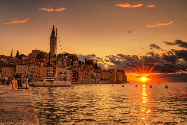 Beautiful colorful sunset Rovinj Adriatic sea Croatia, moving clouds and reflection in the water