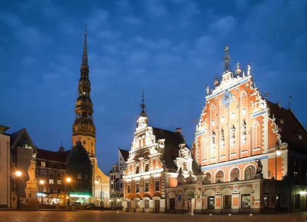 Beautiful old architecture of the central square of Riga. Night view with blue cloudy sky in background and illuminated buildings in foreground