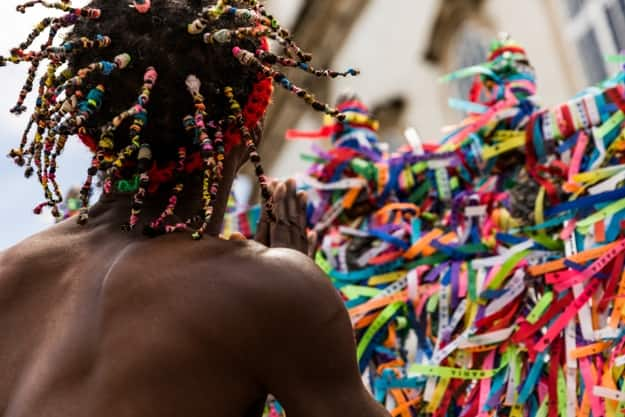 Brazilian afro man making a wish with the colorful religious brazilian ribbons
