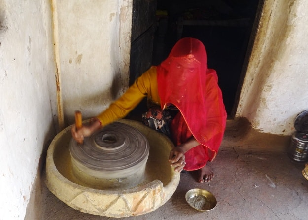 A woman in Bishnoi village operates the stone mill