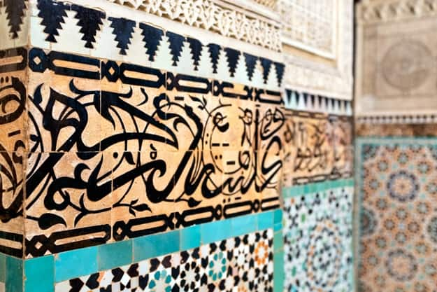 Islamic calligraphy detail. Traditional Arabic Coranic Calligraphy in the madrasa Bou Inania, Meknes, Morocco