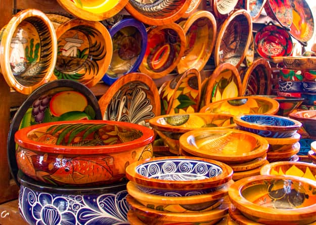 Mexican pottery in bold earthy colors and patterns. At artisan market in Puerto Vallarta, Mexico.