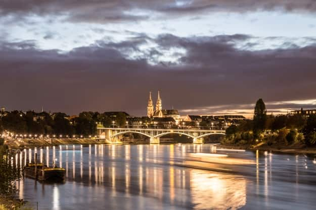 Night view of the Rhine River with the illuminated Basel Minster