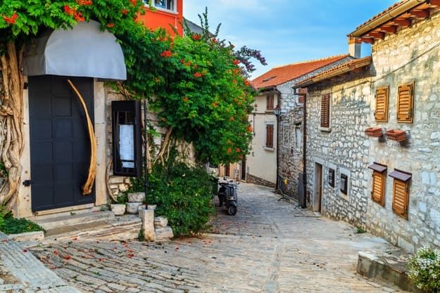 Spectacular stone paved street and restaurant entrance with colorful mediterranean flowers, Rovinj old town,Istria region,Croatia,Europe