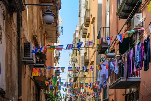 Streets of Naples, June 11, 2016 in Naples, Italy. Many international small flags hanging from ropes along streets