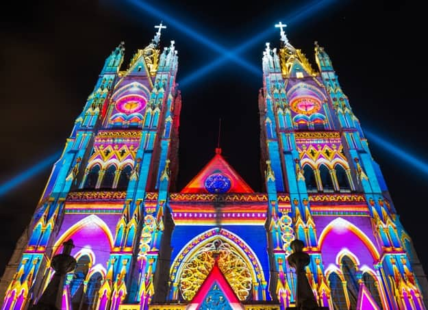 The neo - gothic style Basilica of the National Vow (Basilica del Voto Nacional) illuminated with colorful lights during the Quito light festival